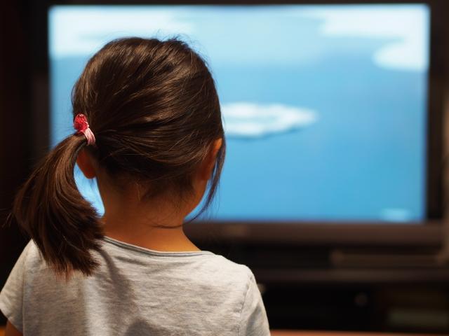 女の子がテレビを見ている画像